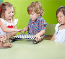 toddler playing a musical instrument while others are watching